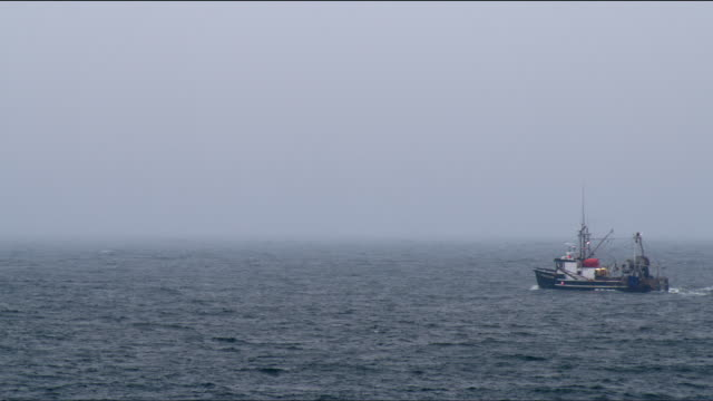Commercial fishing boat out to sea in gloomy weather and rough seas - wide shot with foggy horizion