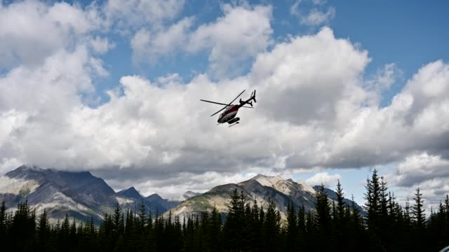 commercial helicopter flying into rocky mountains at assiniboine provincial park - rescue stock videos & royalty-free footage