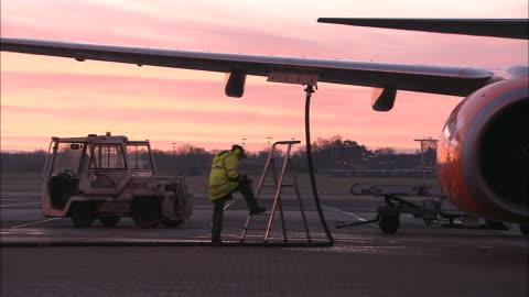 vídeos y material grabado en eventos de stock de ms commercial jet being refueled on tarmac at dawn, belfast airport, ireland, united kingdom - echar combustible