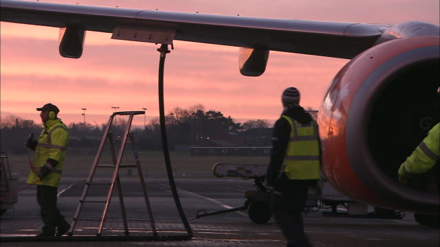 ms commercial jet being refueled on tarmac at dawn, belfast airport, ireland, united kingdom - tanken stock-videos und b-roll-filmmaterial