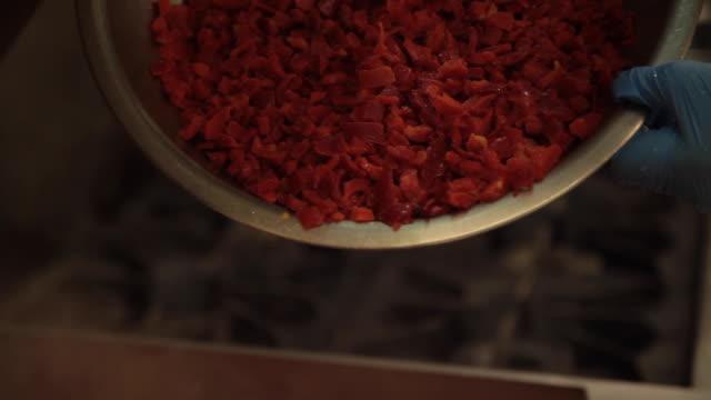vidéos et rushes de préparation commerciale des aliments de cuisine - poivrons rouges congelés placés dans un skillet de 30 gallons - aliment en portion