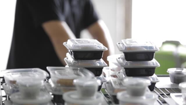 vídeos de stock e filmes b-roll de commercial kitchen food preparation - packing prepared meals - social worker