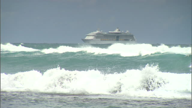 commercial multilevel tourist vacation cruise ship offshore on ocean/sea, choppy white cap waves & exposed water boulder rocks fg. no people,... - boulder rock video stock e b–roll