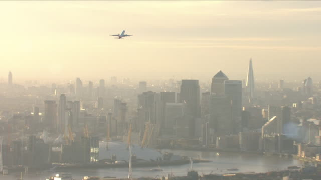 commercial plane flying over londonon a foggy day - luftverschmutzung stock-videos und b-roll-filmmaterial