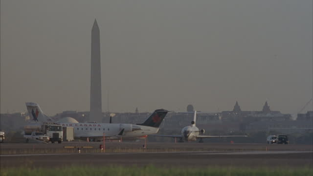 commercial planes taxi at reagan national airport near the washington monument. - ronald reagan washington national airport stock videos & royalty-free footage