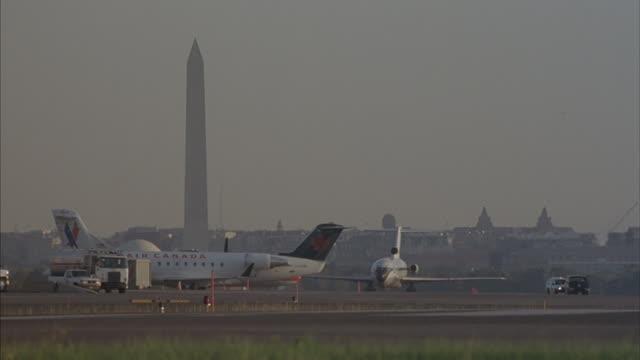 commercial planes taxi at reagan national airport near the washington monument. - ロナルド レーガン ワシントン国際空港点の映像素材/bロール
