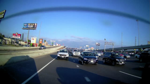 commercial signs and rear camera point of view of driving in rush hour in houston texas - rear view stock videos & royalty-free footage