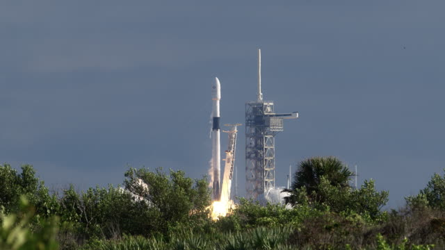 commercial space rocket launches into the blue sky and clouds from cape canaveral - rakete stock-videos und b-roll-filmmaterial