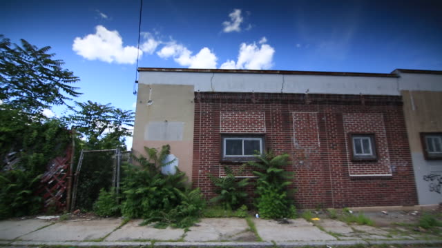 commercial street empty lots w/ overgrown weeds behind fences brick building w/ graffiti on wall factory smokestack warehouse - lowell stock videos & royalty-free footage