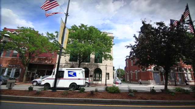 commercial street, mid-rise buildings w/ storefronts, several empty, canal, parked cars, passing post office truck & yellow school bus, median strip... - post office stock videos & royalty-free footage