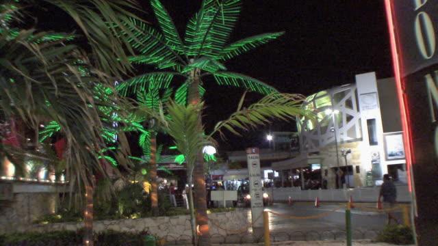 vídeos y material grabado en eventos de stock de ws commercial strip at night with palms in foreground / cancun, quintana roo, mexico - quintana roo