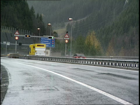 a commercial vehicle stops for a traffic signal on a wet swiss highway. - wet wet wet stock videos & royalty-free footage