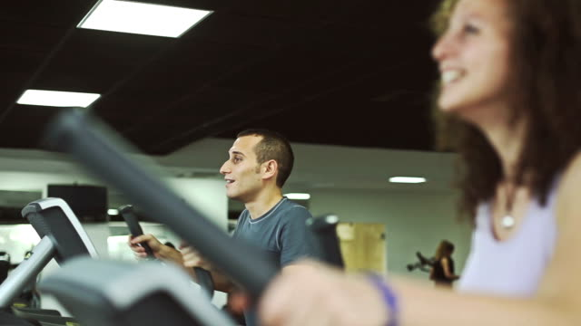 Common people training on a cardio machine