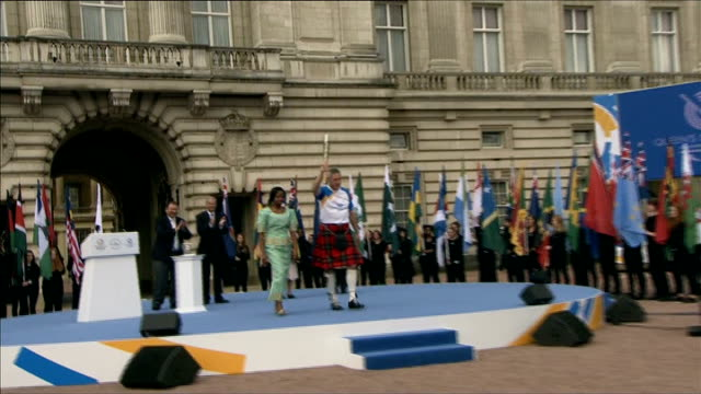 vidéos et rushes de commonwealth games baton relay starts various of allan wells lifting baton and along wells passing baton on to baton holder at gates of buckingham... - par équipe