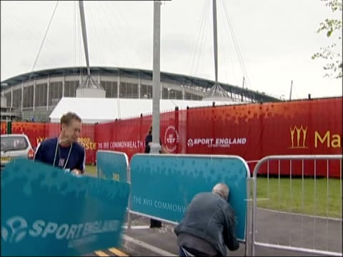 commonwealth games open; itn england: manchester ext 'manchester 2002' flag on lamp post tilt down to workers putting up barriers outside stadium two... - commonwealth games stock videos & royalty-free footage