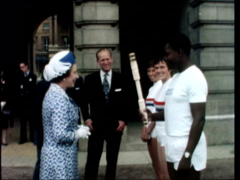 queen hands over baton:; england: london: buckingham palace: ext queen elizabeth ii hands baton to runners - run out palace: handover in hyde park to... - commonwealth games stock videos & royalty-free footage