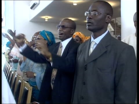 vídeos de stock, filmes e b-roll de zimbabwe to remain suspended; bill neely nigeria: abuja: int group dancing and singing at church service mss congregation singing along ext tony... - prime minister