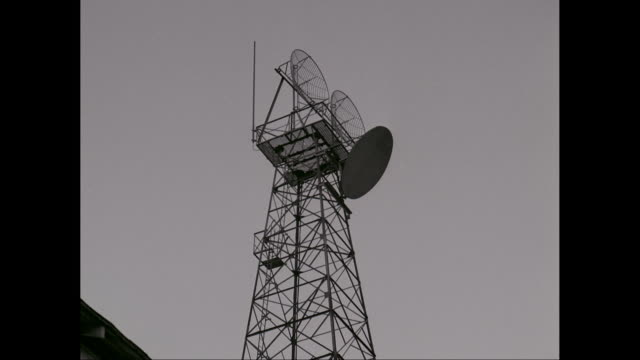ms tu communication tower with satellite dish against sky / united states - sendeturm stock-videos und b-roll-filmmaterial