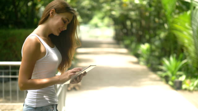 communication : young woman using tablet outdoor - e reader stock videos & royalty-free footage