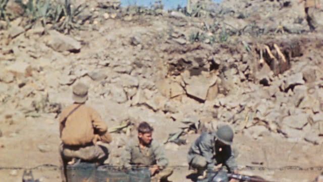 communications section splicing wire protected by infantry and soldiers in base camp below ridge / iwo jima japan - schlacht um iwojima stock-videos und b-roll-filmmaterial