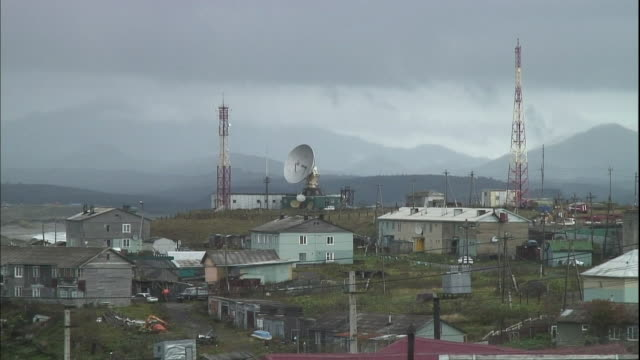 communications towers and a parabola are positioned near buildings on a kunashiri island hilltop. - mast stock videos & royalty-free footage