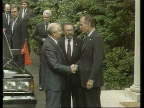 usa reaction ext england london ambassador's residence tms soviet pres mikhail gorbachev along pan lr pull out shakes bush zoom bv gorbachev chatting... - 改革点の映像素材/bロール