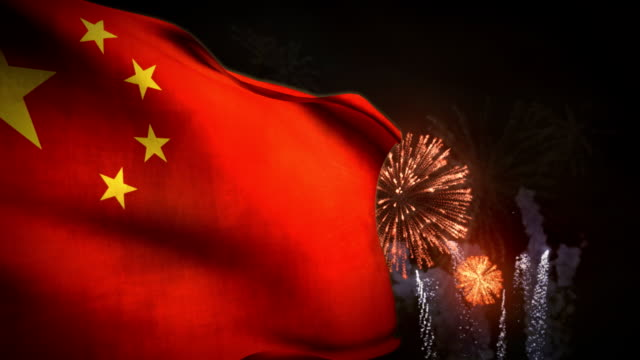 vídeos de stock e filmes b-roll de a communist china flag waves in the wind as fireworks explode behind it. - comunismo