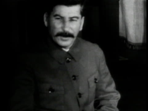 vídeos de stock e filmes b-roll de communist dictator josef stalin premier of the soviet union seated talking to people off camera gesturing w/ fingers to chest while talking. - 1935