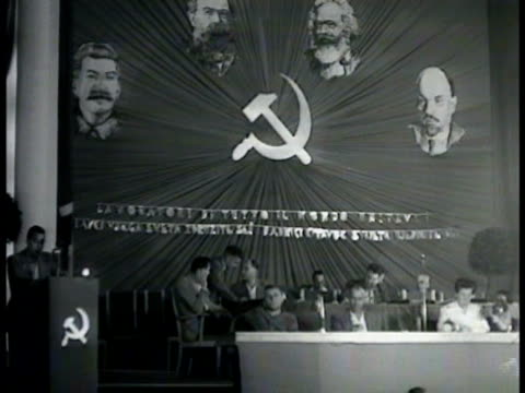 stockvideo's en b-roll-footage met communist party meeting w/ people sitting on stage near podium framed illustration of joseph broz tito on wall draped below w/ trieste flag - 1948