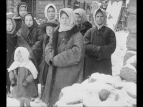 communist revolutionary vladimir lenin sits in chair talks while stroking cat / russian women and children stand outside wearing overcoats and... - ex unione sovietica video stock e b–roll