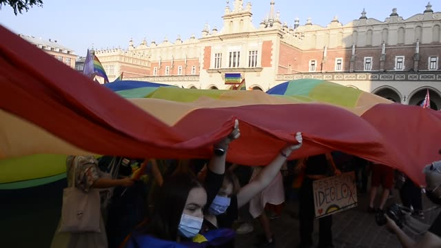 community and supporters wear protective face masks and dance under a giant rainbow flag during the 2020 equality march on the unesco listed main... - poland stock videos & royalty-free footage