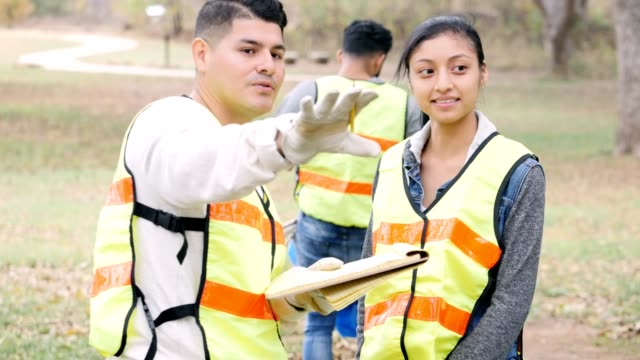 Community cleanup volunteer coordinator gives instructions to female volunteer