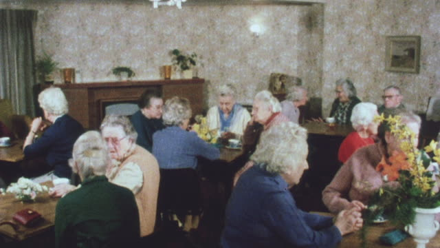 1983 montage community living center for elderly, with residents in living area, visitor using voice announcement for controlled entrance, and residents in private living area / birmingham, england, united kingdom - community center stock videos and b-roll footage