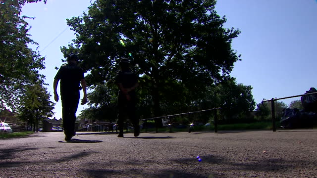 """community police officers patrolling park in bristol to explain and enforce the new rule of six coronavirus rule - """"bbc news"""" stock videos & royalty-free footage"""