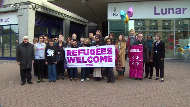Community volunteers holding up signs welcoming child refugees to London