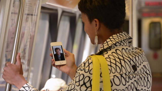 CU Commuter in Subway Train Using Smart Phone to Video Conference / Alexandria, Virginia, USA