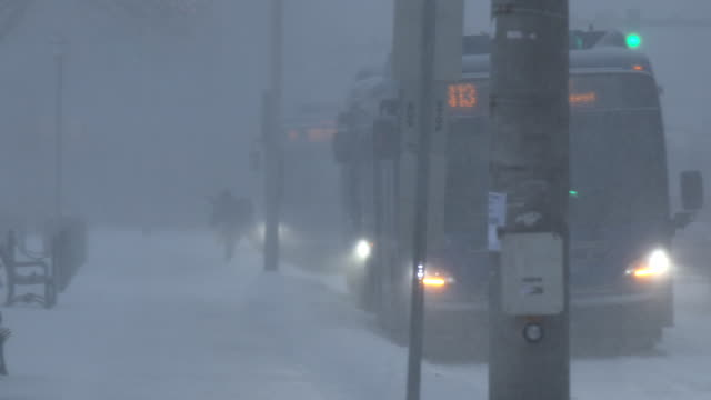 A commuter in Waterbury Connecticut struggles and stumbles in deep snow as they get off a city bus during morning rush hour as heavy snow and strong...