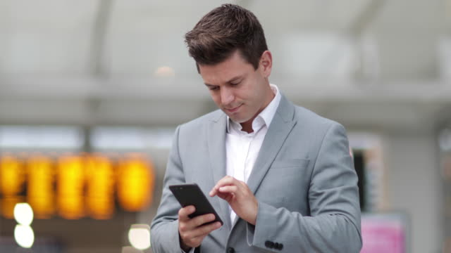 Commuter looking at train times at station holding smartphone