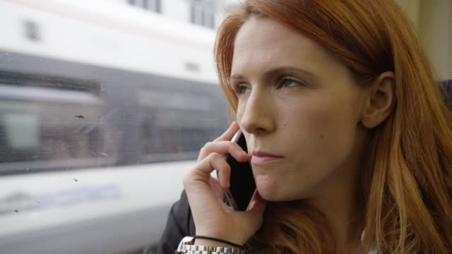 Commuter on her way to work looking out of the window and using smartphone