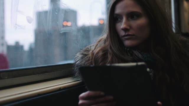Commuter on subway train in New York holding digital tablet