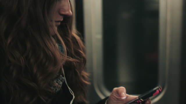 Commuter on subway train in New York looking at smart phone