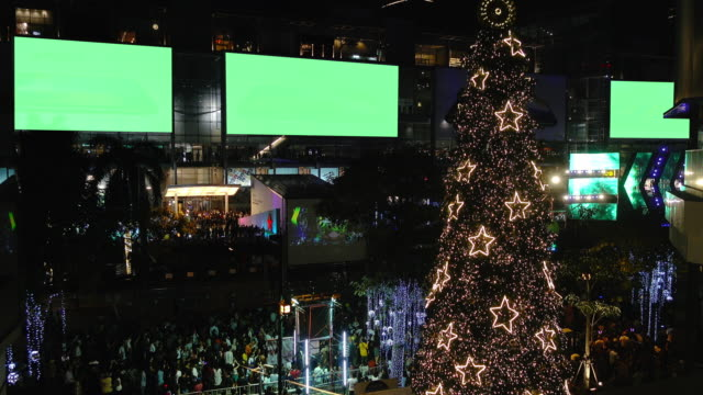 Multitud de peatones de viajero con árbol de Navidad al aire libre