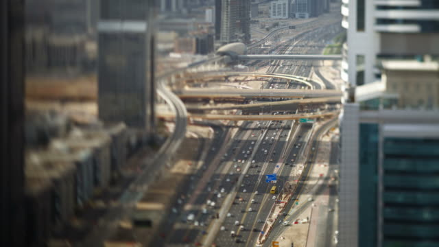 Commuter traffic bustles on Sheikh Zayed Road past an interchange and public railways in downtown Dubai.
