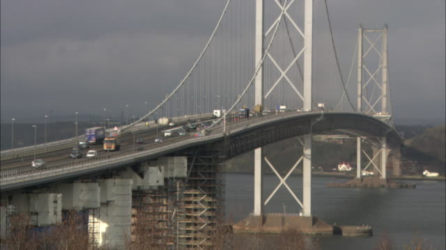 commuter traffic crosses the firth of forth on a suspension bridge. - fluss firth of forth stock-videos und b-roll-filmmaterial
