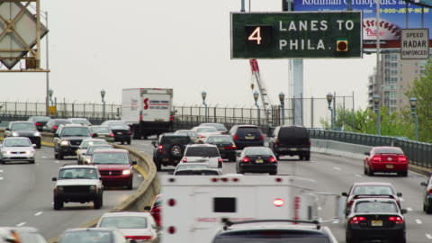 """commuter traffic flows around a curve toward the city; highway sign reads """"4 lanes to philadelphia."""" - philadelphia pennsylvania stock videos & royalty-free footage"""