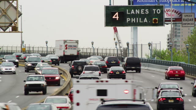 "commuter traffic flows around a curve toward the city; highway sign reads ""4 lanes to philadelphia."" - philadelphia pennsylvania stock videos & royalty-free footage"