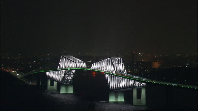vidéos et rushes de commuter traffic uses the illuminated tokyo gate bridge to cross tokyo bay. - phare de véhicule