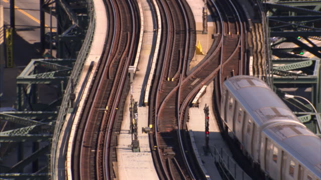 A commuter train approaches the rail yard on a winding track.