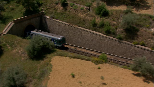 a commuter train exits a tunnel and travels across beautiful countryside near sicily, italy. - ferrovia video stock e b–roll