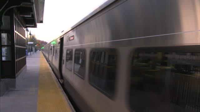 A commuter train leaves Hudson Station as another train slowly comes to a stop.